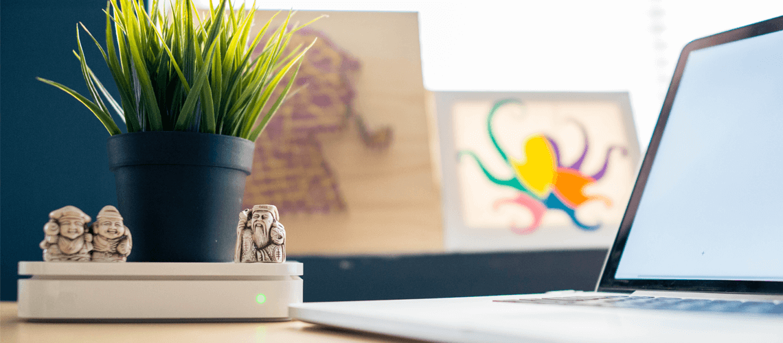 laptop on a desk surrounded by a potted plant, some small figurines and a colourful abstract picture