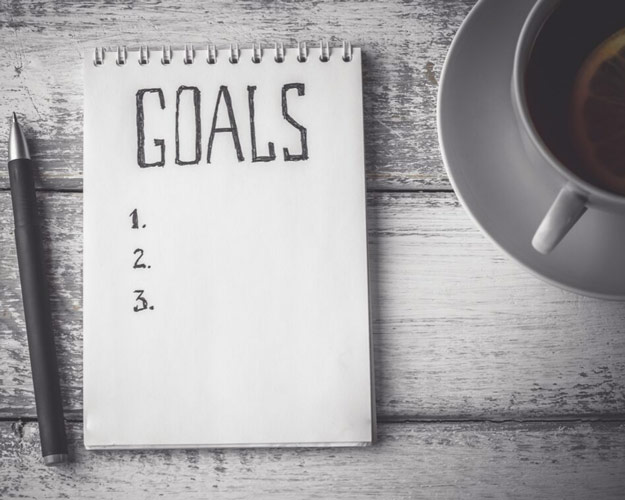 notepad with text stating goals