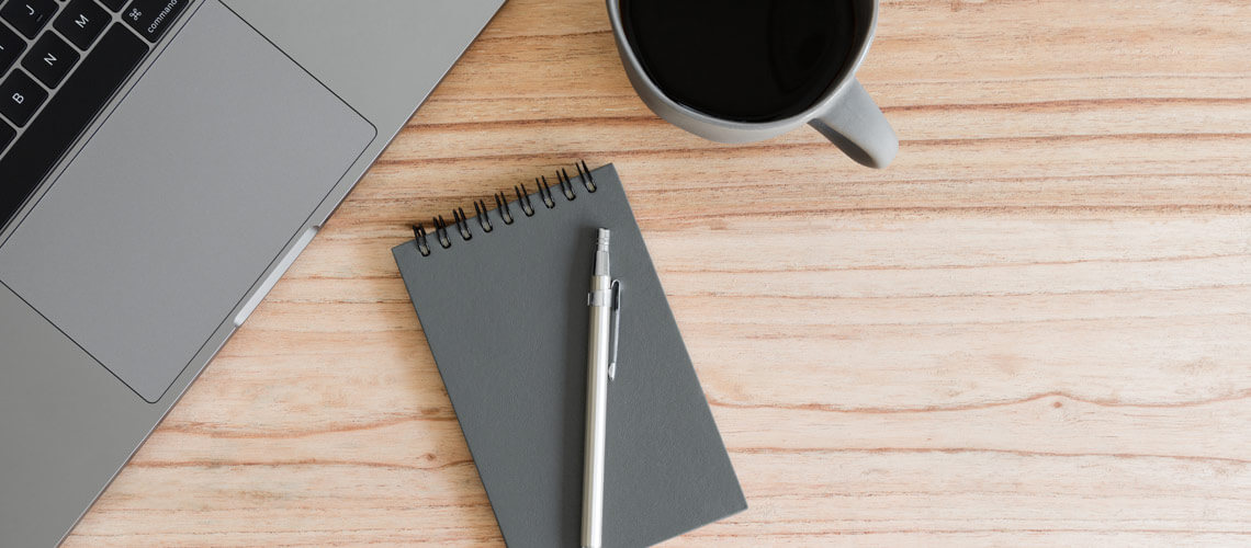 laptop notepad and coffee on wooden desk