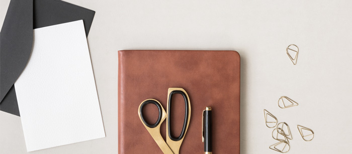 Featured image for blog post simple ways to customize stock photos showing a journal, scissors, pen with some stationery