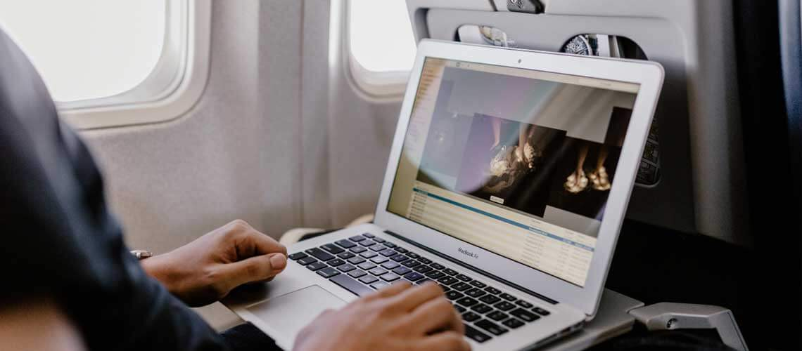man with laptop on airplane