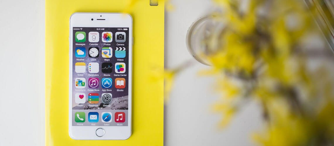 white IPhone on a yellow notepad with yellow flowers in background